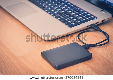 transfer or backup data between laptop and external hard disk on office desktop still life