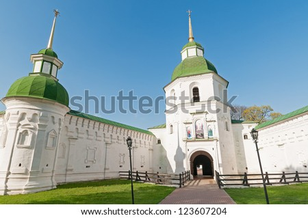 Transfiguration cathedral and wooden tower with lawn and paved road before against blue sky background. Novgorod-Siversky, Ukraine.