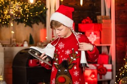 Transform your shoes into ice skates for Winter. New year party. Christmas mood concept. Santa claus kid. Happy winter holidays. Christmas coming. Small boy. Little boy child in santa red hat.