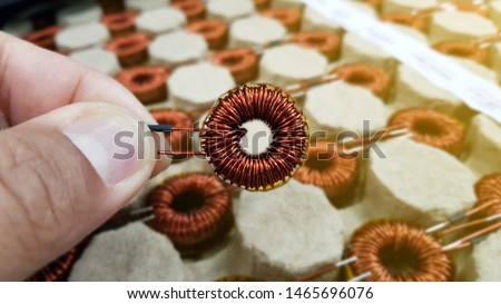 Transformer coil in hand,Toroidal Coil Inductor,Copper wire winding, Magnetic ferrite core,Electromagnetic coil, inductor on circuit board close-up