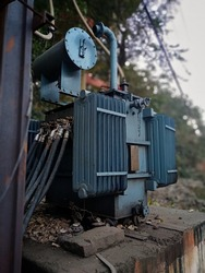 Transformer : The equipment used to raise or lower voltage, high voltage power station. high-voltage substation on blue sky background with switch.Medium voltage transformer with electrical insulation