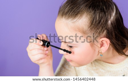 Transforming her eyes with the power of mascara. Small child using mascara brush for enhancing eyelashes. Little girl applying eye mascara. Cute baby doing her eye makeup with black mascara.
