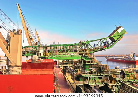 Transhipment terminal for discharging bulk cargo of chemical sulphur from ships using a shore crane. Port of Jorf-Lasfar, Morocco. July, 2017.