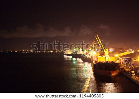 Transhipment terminal for discharging cement cargo by shore cranes. A view of berths with cargo ships and the water area of the port of Abidjan, West Africa.