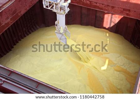 Transhipment terminal for loading bulk cargo of chemical sulphur to sea bulk carriers using a shore crane. Port Beaumont, Texas, USA. July, 2017.