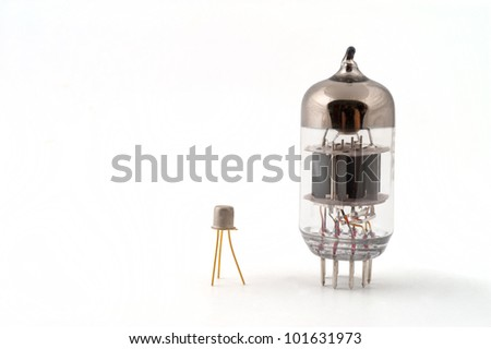 Transistor next to a vacuum tube on a white background