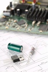 Transistor, resistor and capacitor electronic parts or components in front of pcb board with pcb wiring diagram - electronic device repair concept, selective focus