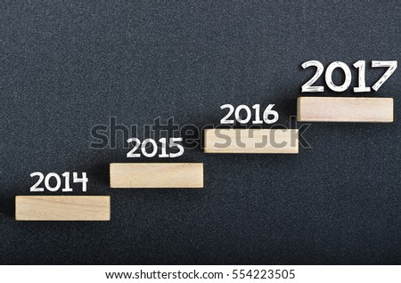 Transition from year 2014 until  2017 concept: Text written on wooden square  blocks #554223505