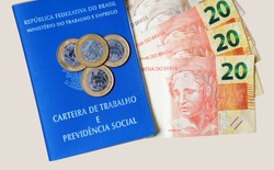 Translation: Federative Republic of Brazil, Ministry of Labor. / Brazilian Work Card (Carteira de Trabalho) and Brazilian money. Real banknotes and coins. Salary concept.