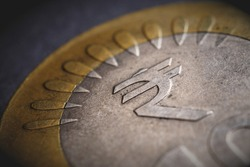Translation of the inscription: rupee. Fragment of Indian 10 rupee coin with the sign of the national currency. Dramatic illustration with vignetting. Money, economy and banking in India. Macro