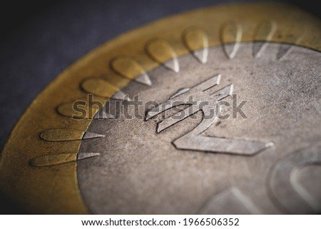 Translation of the inscription: rupee. Fragment of Indian 10 rupee coin with the sign of the national currency. Dramatic illustration with vignetting. Money, economy and banking in India. Macro Stockfoto ©