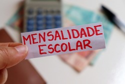 Translation: Tuition (mensalidade escolar). | Hand holding note with mensalidade escolar (tuition) written and calculator, Brazilian money and wallet in the background. School tuition fees in Brazil.