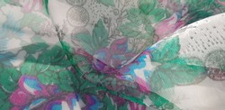 Translucent slightly shiny fabric with pink-blue-green floral print and gray border, in folds (texture).