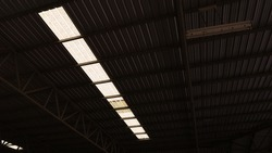 Translucent tiles on the roof. Sunlight shines through the translucent roof panels to add light in the warehouse or factory in the bottom view with copy space. Selective focus