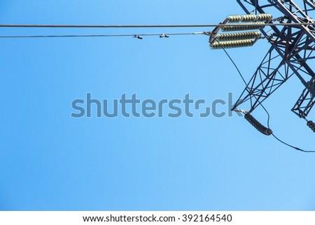 transmission line tower, against blue sky