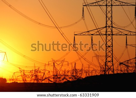 transmission tower   against the sun during sunset