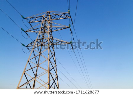 Transmission tower, or power line, in front of a clear blue sky, on a sunny day. These are scattered throughout the UK, so that people can make landline phone calls to others, via a wired connection. Stok fotoğraf ©