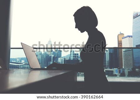 Transmit and manipulate data concept. Female thief is stealing information from portable net-book. Silhouette of business woman is sitting behind a laptop computer screen and connecting to internet