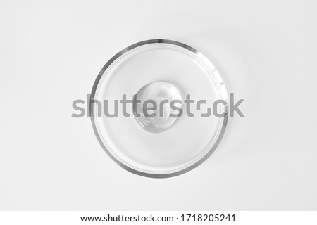 Transparent aloe gel in glass petri dish on white background. Concept laboratory tests and research, making cosmetic. Purity facial cleanser, peeling, shampoo or shower gel