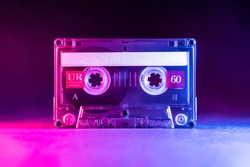 Transparent audio cassette tape lit by pink and blue lamps on a black background. Front, top view.