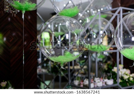 Transparent balloons with green feathers inside hangs on the party