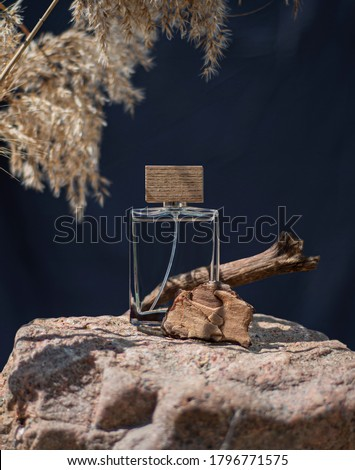 Transparent bottle of perfume on a background of stone and wood. Beige and blue perfume presentation. Trending concept in natural materials.  Women's and men's essence. Natural cosmetic Foto stock ©