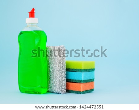 Transparent bottle with green dishwashing liquid and four foam sponges of different colours on a blue background. Copy space. Kitchen detergent. Household chemicals. Household chores. #1424472551