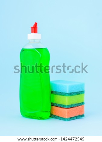 Transparent bottle with green dishwashing liquid and three foam sponges of different colours on a blue background. Kitchen detergent. Household chemicals. Household chores. #1424472545