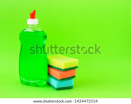 Transparent bottle with green dishwashing liquid and three foam sponges of different colours on a green background. Copy space. Kitchen detergent. Household chemicals. Household chores. #1424472554