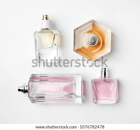 Transparent bottles of perfume on white background