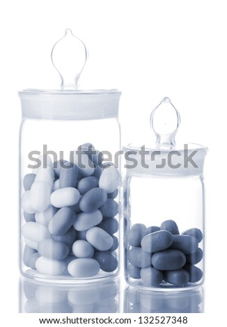Transparent bottles with pills in grey light isolated on white