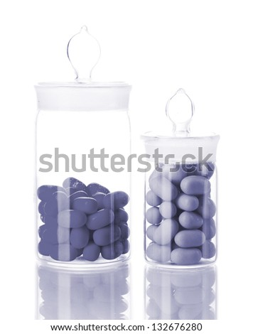 Transparent bottles with pills in grey light isolated on white - stock photo