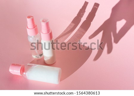 Transparent cosmetic bottles on a pink background with spectacular shadows. Also the shadow of a female hand. The concept of cosmetology, the choice of cosmetics, face and body skin care. Minimalism.