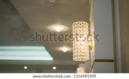 Transparent crystal round chandelier, sconce lamp with edison bulb on wall with small triangular graphic black and white tiles. Concept interior loft, modern design restaurant, apartment, room, store