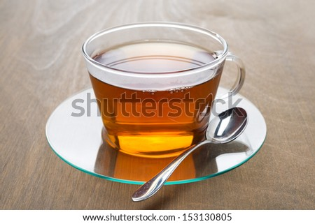 Transparent cup of black tea on wooden background, horizontal