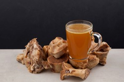 Transparent Cup of bone broth is placed on boiled beef bones, which contain the necessary amino acids for the body. Selective focus