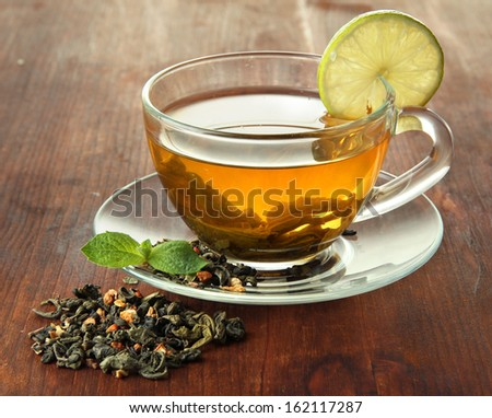 Transparent Cup Of Green Tea With Lime On Wooden Background