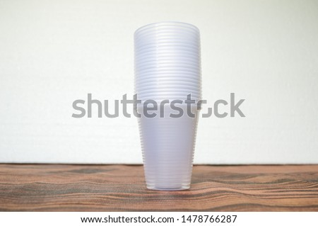 transparent disposable plastic cups on wooden table #1478766287