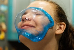 Transparent elastic mucus on the face of a happy young woman close-up. A cheerful, laughing girl looks through the blue slime. A game with a popular sticky anti-stress toy made by hand. A fun holiday