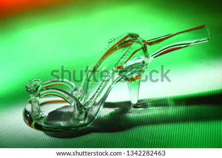 1861934c14e Transparent empty glass bottle shaped as woman sandals with high hill in  green and red light