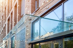 Transparent glass awning over front door of multistory brick apartment building