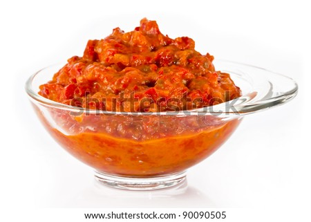 Transparent glass bowl full of delicious ajvar, on a white background.
