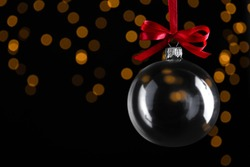 Transparent glass Christmas ball against dark background with festive lights. Space for text