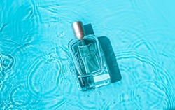 Transparent glass cosmetic perfume bottle in the blue water . Top view