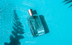 Transparent glass cosmetic perfume bottle in the blue water under shadows of tropical leaves. Top view