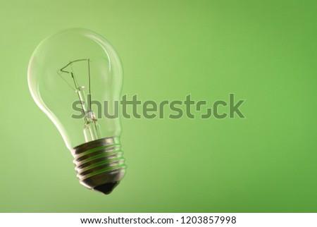Transparent glass lightbulb on green background. Lightbulb on green. Traditional lightbulb.