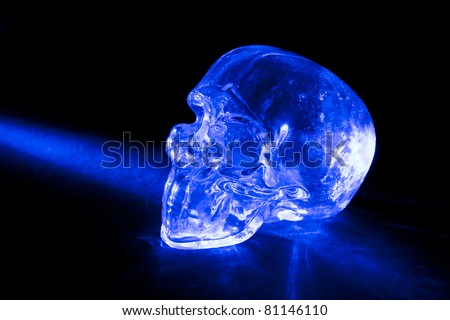 Transparent glass skull with blue light ray against black background.