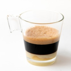 transparent glass tumbler with a coffee with foam and condensed milk in the background. Caffè crema - cream coffee