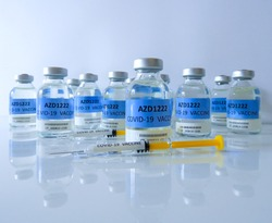 Transparent glass vials with test COVID-19 vaccine, named AZD1222 and two glass syringes with yellow pistons on white surface and white background. Selected focus.