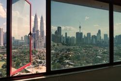 Transparent glass windows look like views of Kuala Lumpur city during sunny days.